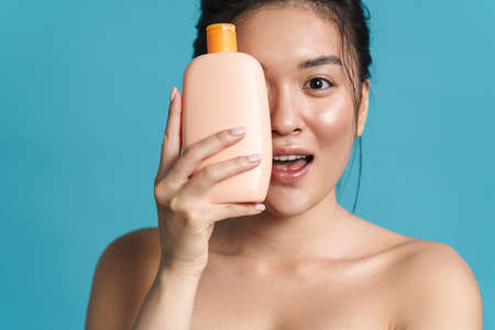Image of excited shirtless asian girl posing with shampoo isolated over blue background 版權商用圖片