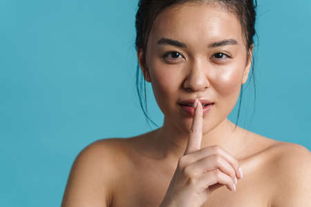 Image of shirtless asian girl showing silence gesture at camera isolated over blue background