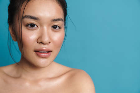Image of shirtless asian girl posing and looking at camera isolated over blue background