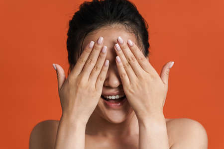 Image of shirtless asian girl smiling and covering her eyes isolated over orange background