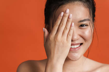Image of shirtless asian girl smiling and covering her eye isolated over orange background