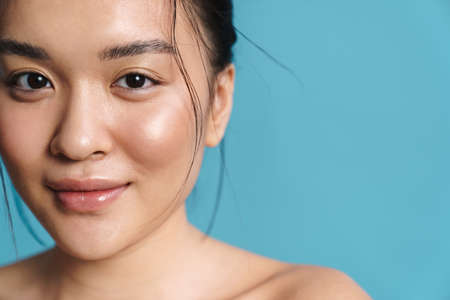 Image of shirtless asian girl smiling and looking at camera isolated over blue background