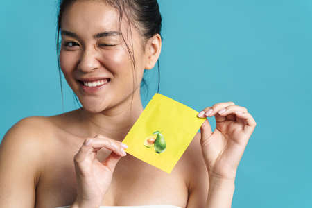 Image of cheerful shirtless asian girl winking while holding face mask isolated over blue background 版權商用圖片