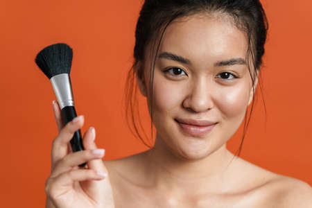 Image of cheerful shirtless asian girl posing with powder brush isolated over orange background