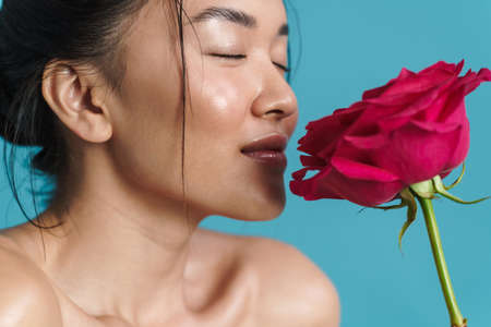 Image of pleased shirtless asian girl smelling rose isolated over blue background 版權商用圖片