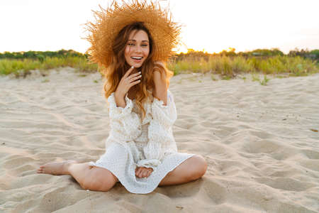 Young caucasian attractive brunette woman in dress smiling while sitting on beach