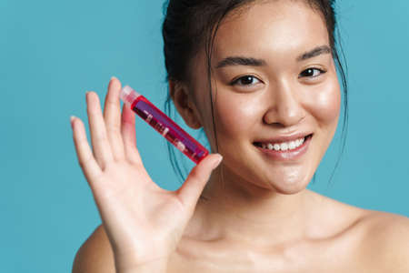 Image of happy shirtless asian girl posing with facial serum isolated over blue background