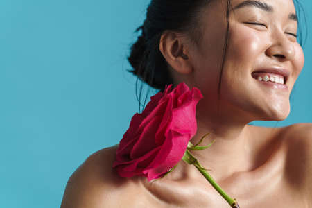Image of shirtless asian girl smiling while posing with rose isolated over blue background