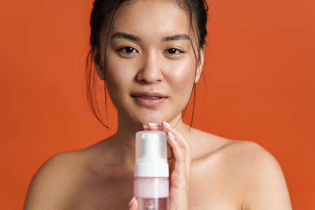 Image of pleased shirtless asian girl posing with cleansing foam isolated over orange background