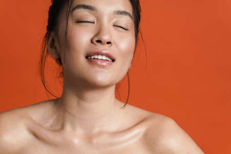 Image of shirtless asian girl posing and smiling at camera isolated over orange background