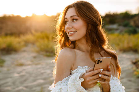 Young caucasian attractive brunette woman smiling and holding cellphone while walking outdoors