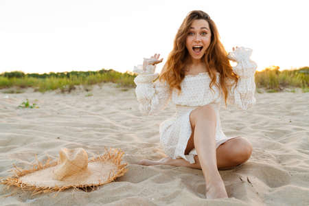 Young caucasian attractive brunette woman in dress laughing while sitting on beach 版權商用圖片