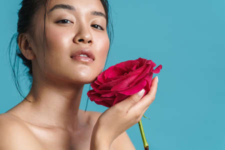 Image of pleased shirtless asian girl posing with rose isolated over blue background 版權商用圖片