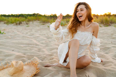 Young caucasian attractive brunette woman in dress smiling and waving while sitting on beach