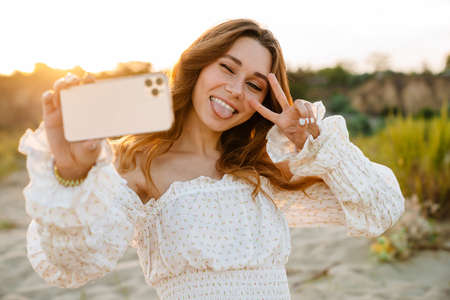 Young caucasian attractive brunette woman smiling and taking selfie photo on cellphone outdoors 版權商用圖片