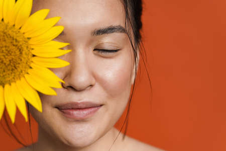Image of shirtless asian girl smiling while posing with sunflower isolated over orange background 版權商用圖片