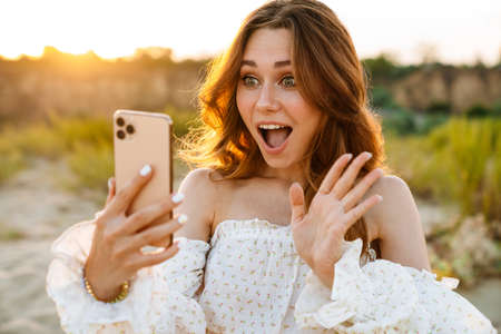 Young caucasian attractive brunette woman smiling and waving at cellphone outdoors