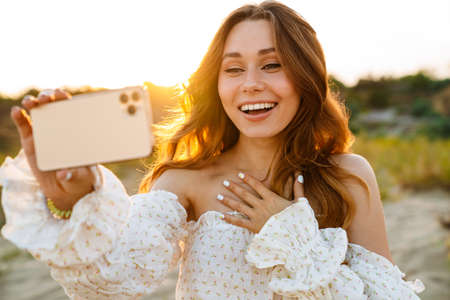 Young caucasian attractive brunette woman smiling and taking selfie phoro on cellphone outdoors 版權商用圖片