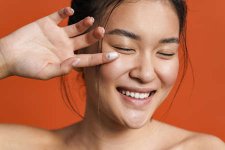 Image of laughing shirtless asian girl applying facial cream isolated over orange background 版權商用圖片