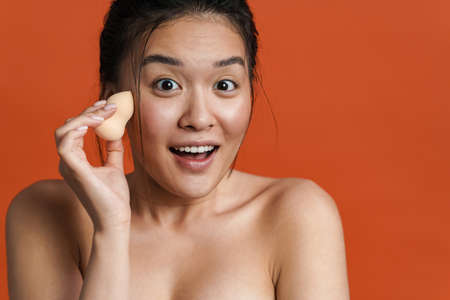 Image of excited shirtless asian girl using cosmetic sponge isolated over orange background