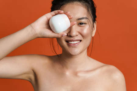 Image of smiling shirtless asian girl posing with facial cream isolated over orange background