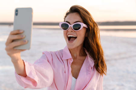 Image of a cute surprised shocked young girl in sunglasses taking a selfie by phone outdoors at the beach