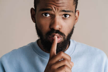 Confused african american guy showing silence gesture on camera isolated over white background Imagens