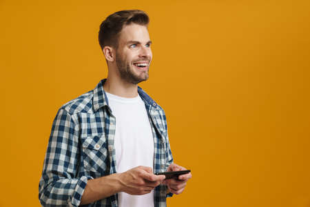 Caucasian cheerful guy playing online game on mobile phone isolated over yellow background