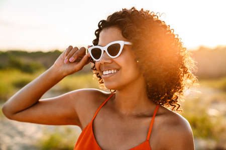 Image of amazing beautiful happy young african woman walking at the beach outside in sunglasses