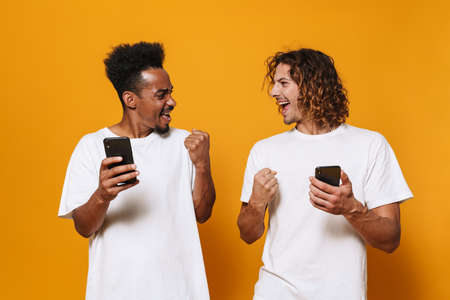 Excited multicultural two guys using smartphones and making winner gesture isolated over yellow background