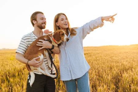 Image of optimistic happy young loving couple walking with dog outside at the field while pointing aside