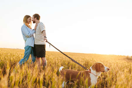 Photo of a happy young loving couple walking with dog outside at the field