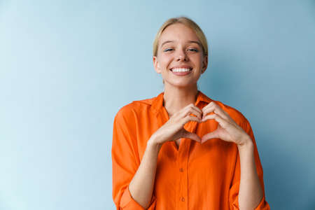 Joyful beautiful girl showing heart gesture and smiling isolated over blue background 免版税图像