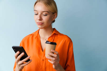 Focused beautiful girl using mobile phone and drinking coffee isolated over blue background 免版税图像