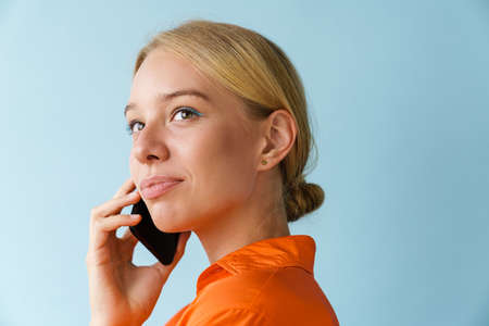 Pleased beautiful blonde girl talking on mobile phone isolated over blue background 免版税图像