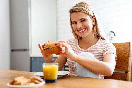 Smiling young woman eating hamburger at the kitchen at home