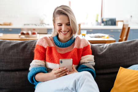 Attractive smiling young woman using mobile phone while ralaxing on couch at home