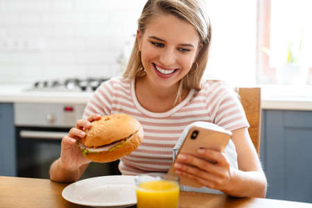 Smiling young woman eating a hamburger at home and using mobile phone