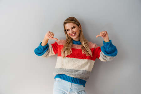 Portrait of a happy young woman pointing fingers at herself isolated over white background