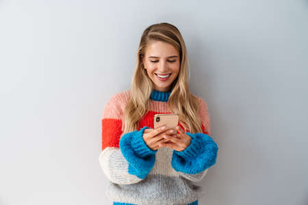 Smiling young woman using smartphone over gray background