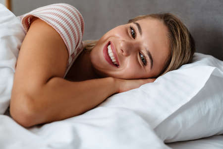 Young happy smiling woman waking up at the bedroom