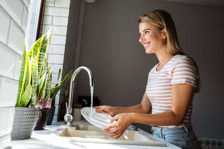 Beautiful smiling young woman washes dishes while cleaning in kitchen