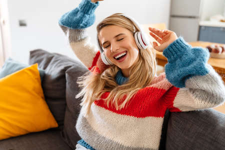 Happy young woman sitting on sofa listening to music with headphones, dancing