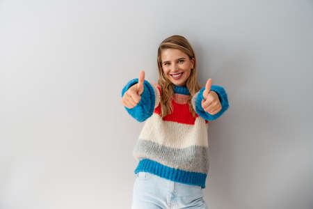 Cheerful casual woman standing isolated on white background, showing thumbs up
