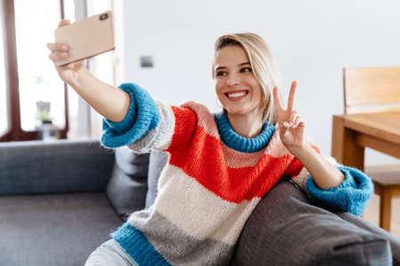 Happy young woman taking a selfie while sitting on a couch at home