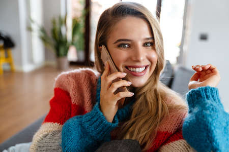 Attractive smiling young woman using mobile phone while ralaxing on couch at home, talking