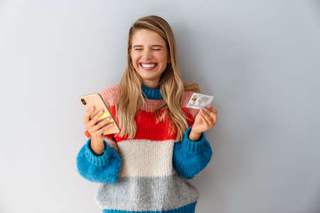 Laughing blonde woman holding cellphone and credit card isolated over gray background, celebrating