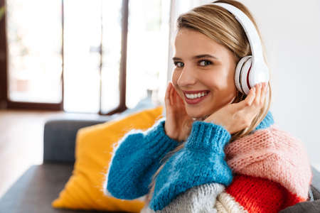 Happy young woman sitting on sofa listening to music with headphones