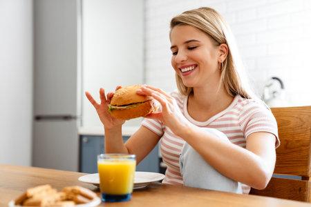 Cute young woman eating a hamburger at home and smiling
