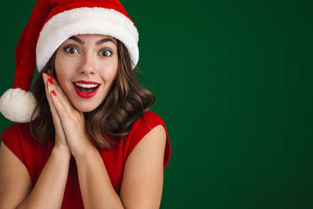 Beautiful excited girl in Santa Claus hat smiling and looking at camera isolated over green background